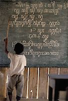 Boy pointing at writing on a blackboard in a rural school Stock Photo - Premium Rights-Managednull, Code: 832-03724424