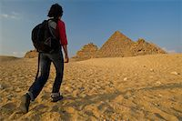 Woman with rucksack walking towards Pyramids at dusk Stock Photo - Premium Rights-Managednull, Code: 832-03724769