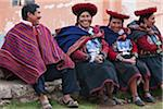 Peru, A man shares a joke with a group of native Indian women in traditional costume. Their saucer-shaped hats, beautifully decorated red jackets, black skirts and hand-woven woollen blankets round their shoulders are typical of the region. Stock Photo - Premium Rights-Managed, Artist: AWL Images, Code: 862-03732055