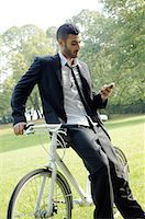 Businessman with bicycle and cell phone in park Stock Photo - Premium Royalty-Freenull, Code: 689-03733401