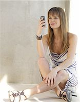 Woman in striped dress using cell phone Stock Photo - Premium Royalty-Freenull, Code: 689-03733683