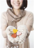 Woman holding wooden hearts Stock Photo - Premium Royalty-Freenull, Code: 670-03734372
