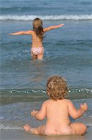 Naked Baby Sitting on Beach and Girl with Outstretched Arms Wading in Water Stock Photo - Premium Rights-Managednull, Code: 700-03739260
