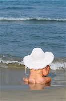 Baby Girl Sitting on Beach Wearing Large Sunhat Stock Photo - Premium Rights-Managednull, Code: 700-03739261