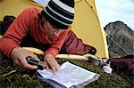 Woman in a tent consults a GPS and map while camping at Rabbit Lake, Chugach State Park, Southcentral Alaska, Autumn Stock Photo - Premium Rights-Managed, Artist: AlaskaStock, Code: 854-03739547