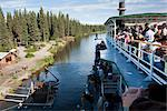 Tourists on board the Riverboat Discovery  view the Chena Indian Village, a mock-village on the Riverboat Discovery tour along the Chena River, Fairbanks, Interior Alaska, Summer Stock Photo - Premium Rights-Managed, Artist: AlaskaStock, Code: 854-03739780
