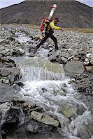 Backpacker crosses a creek in the Katak Creek valley returning from Mt. Chamberlin ski descent, Brooks Range, ANWR, Arctic Alaska, Summer Stock Photo - Premium Rights-Managednull, Code: 854-03740070