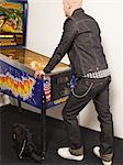 A man wearing denim playing flipper. Stock Photo - Premium Royalty-Free, Artist: Gail Mooney, Code: 6102-03750515