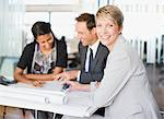 Business people looking at blueprints together Stock Photo - Premium Royalty-Freenull, Code: 635-03752298