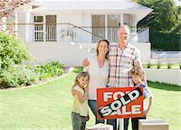 sold sign - Family standing with sold sign of their new house Stock Photo - Premium Royalty-Freenull, Code: 635-03752510