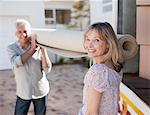Couple carrying carpet from moving van Stock Photo - Premium Royalty-Freenull, Code: 635-03752518
