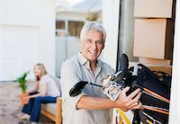 Man removing golf clubs from moving van Stock Photo - Premium Royalty-Freenull, Code: 635-03752546