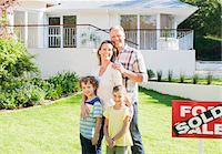 sold sign - Family standing in front yard of new house next to sold sign Stock Photo - Premium Royalty-Freenull, Code: 635-03752591