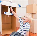Grinning boy playing with model airplane in his new house Stock Photo - Premium Royalty-Free, Artist: Cultura RM, Code: 635-03752598