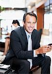 Businessman text messaging on cell phone in hotel lobby Stock Photo - Premium Royalty-Freenull, Code: 635-03752691