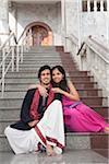 Portrait of Couple Sitting on Steps at Vishnu Temple, Bangkok, Thailand