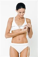 Young woman measuring breasts with tape measure Stock Photo - Premium Royalty-Freenull, Code: 614-03763589