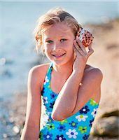 preteen girl swimsuit - Girl listening to shell at the beach Stock Photo - Premium Royalty-Freenull, Code: 649-03769758