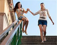 Young women sliding down railing Stock Photo - Premium Royalty-Freenull, Code: 649-03769776