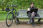 Woman looking at laptop and eating lunch Stock Photo - Premium Royalty-Freenull, Code: 649-03771450