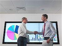 Businessmen shake hands with screen Stock Photo - Premium Royalty-Freenull, Code: 649-03773546
