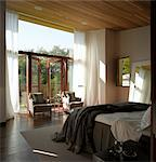 Ad Astra. Master bedroom with wooden floor and ceiling and view past sheer curtains to garden. Architects: Munkenbeck and Marshall Stock Photo - Premium Rights-Managed, Artist: Arcaid, Code: 845-03777235