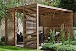 Slatted cedar pavilion on the right side of the lawn on the upper level of the garden. Silver birches along the boundary wall. Hebe and grasses on the right. Architects: Modular Stock Photo - Premium Rights-Managed, Artist: Arcaid, Code: 845-03777659
