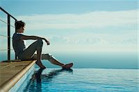 Man sitting on edge of infinity pool, looking at view Stock Photo - Premium Royalty-Freenull, Code: 632-03779622