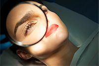 Doctor's Hand Holding Magnifying Glass over Woman's Eye Stock Photo - Premium Rights-Managednull, Code: 822-03780926