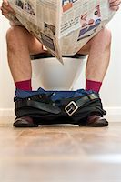 Man Sitting on Toilet Reading Newspaper Stock Photo - Premium Rights-Managednull, Code: 822-03781110