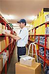 Worker putting boxes on shelves Stock Photo - Premium Royalty-Free, Artist: Ikon Images, Code: 635-03781364