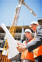 supervising - Construction workers looking at blueprints on construction site Stock Photo - Premium Royalty-Freenull, Code: 635-03781509