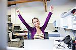 Businesswoman cheering at desk in office Stock Photo - Premium Royalty-Free, Artist: Ikon Images, Code: 635-03781554