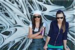 Young Girls Holding Can of Spray Paint in front of Graffiti Covered Wall