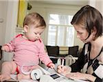 Woman Doing Finances with Baby Girl Stock Photo - Premium Rights-Managed, Artist: Horst Herget, Code: 700-03799542