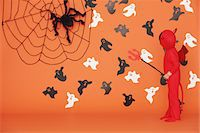 Boy Dressed Up As Devil against Orange Background Stock Photo - Premium Rights-Managednull, Code: 859-03806343