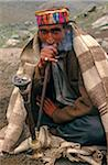 India, Himachal Pradesh, Chamba Valley. A Gaddi (semi-nomadic shepherd) from Chamba smokes a hookah, or water pipe, on the trail linking Kugti village, Kugti Pass and the summer grazing meadows of Lahaul. Stock Photo - Premium Rights-Managed, Artist: AWL Images, Code: 862-03807623