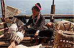 Myanmar, Burma, Keng Tung (Kyaing Tong). An Ann (Enn) lady spinning thread on the platform of her home, with her sleeping baby on her lap, Paunglea village, Keng Tung. Stock Photo - Premium Rights-Managed, Artist: AWL Images, Code: 862-03807942
