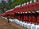 Myanmar, Burma, Pegu, Bago. A line of monk statues leading to Win Sein Taw Ya, the site of the world's largest reclining Buddha image, on the road between Pegu and Mudon. Stock Photo - Premium Rights-Managed, Artist: AWL Images, Code: 862-03807977