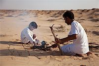 Oman, Wahiba Sands. A Bedouin guide and his son make a fire to make a coffee. Stock Photo - Premium Rights-Managednull, Code: 862-03808149