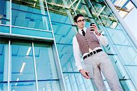 Businessman with Cell Phone Outside of Office Building Stock Photo - Premium Rights-Managednull, Code: 700-03814348