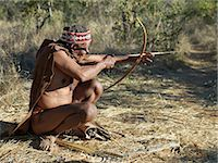 A NIIS hunter gatherer takes aim with his bow and arrow.The arrows are poisoned with the sap of a species of commiphora tree.They have detachable heads and no flights. Until recently, their way of life had remained unchanged for thousands of years.Few now live solely by hunting and gathering. Stock Photo - Premium Rights-Managednull, Code: 862-03820238