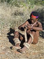 A NIIS hunte gatherer winds strings of rattles round his legs in preparation for a dance.These rattles are made from specially dried cocoons in which are placed tiny chips of stone.The NIIS are a part of the San people, often referred to as Bushmen.They differ in appearance from the rest of black Africa having yellowish skin and being lightly boned, lean and muscular. Stock Photo - Premium Rights-Managednull, Code: 862-03820244