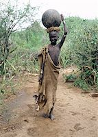 A Mursi girl, accompanied by her dog, carries a large clay pot to collect water from the Omo River. Her earlobes are already pierced and extended, and decorated with round clay discs.She is dressed in skins, attractively decorated with thin stripes.The culture, social organisation, customs and values of the people have changed little. Stock Photo - Premium Rights-Managednull, Code: 862-03820367