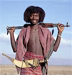 Warriors of the nomadic Afar tribe wear their hair long and carry large curved daggers, known as jile, strapped to their waists.Proud and fiercely independent, they live in the low lying deserts of Eastern Ethiopia.Modern rifles have now replaced daggers as weapons although most young men still wear ornate daggers by tradition. Stock Photo - Premium Rights-Managed, Artist: AWL Images, Code: 862-03820405