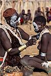 A Karo woman paints her daughters face with white chalk. The mother has styled her hair with mud and ochre. She wears a calfskin cape edged with cowrie shells, and layers of beads, bracelets and amulets. A small Omotic tribe related to the Hamar, who live along the banks of the Omo River in southwestern Ethiopia. Stock Photo - Premium Rights-Managed, Artist: AWL Images, Code: 862-03820422
