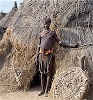 A Karo girl in traditional attire stands outside her familys home.The door of the low entrance to the house is propped against its thatched wall.Most girls pierce a hole below the lower lip in which they place a thin piece of metal or a nail for decoration.The Karo are a small tribe living in three main villages along the lower reaches of the Omo River in southwest Ethiopia. Stock Photo - Premium Rights-Managednull, Code: 862-03820457
