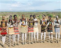 At the start of a dance, Karo men sing and clap in line.The Karo excel in body art. Before dances and ceremonial occasions, they decorate themselves elaborately using local white chalk, pulverised rock and other natural pigments.The Karo are a small tribe living in three main villages along the lower reaches of the Omo River in southwest Ethiopia. Stock Photo - Premium Rights-Managednull, Code: 862-03820494