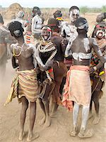 Karo men and girls enjoy a dance.The Karo excel in body art. Before dances and ceremonial occasions, they decorate themselves elaborately using local white chalk, pulverised rock and other natural pigments.The Karo are a small tribe living in three main villages along the lower reaches of the Omo River in southwest Ethiopia. Stock Photo - Premium Rights-Managednull, Code: 862-03820496