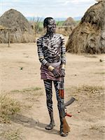 A Kwegu man with his torso decorated with local white chalk.Almost every man owns a gun, usually an AK 47 assault rifle, and keeps spare ammunition in a cartridge belt around his waist.The Kwegu known to the Karo as Muguji, a degoratory name meaning Working Ant, are the smallest tribe living on the banks the Omo River in southwest Ethiopia. Stock Photo - Premium Rights-Managednull, Code: 862-03820503
